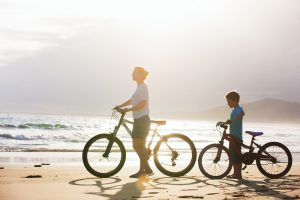 Mother,And,Son,With,Bikes,On,A,Beach,At,Sunset